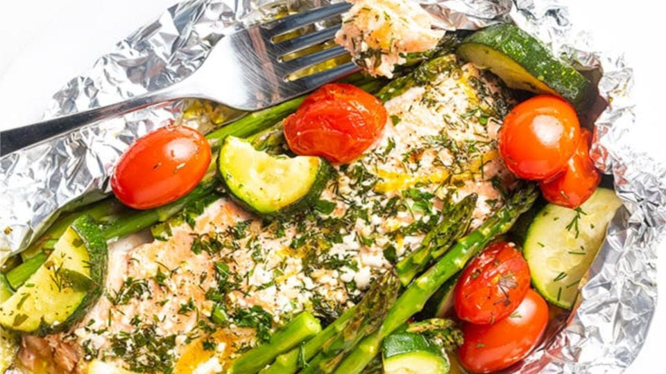 Salmon topped with dill and lemon zest, accompanied by cherry tomatoes, and fresh vegetables all enclosed in tin foil.