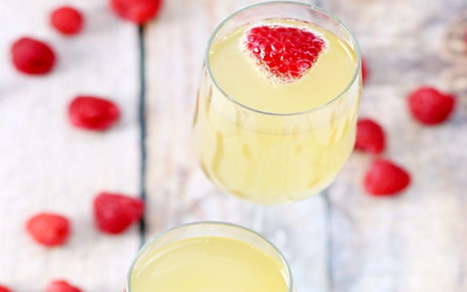 Two champagne flutes filled with mock champagne garnished with a raspberry, with scattered raspberries surrounding the glass.