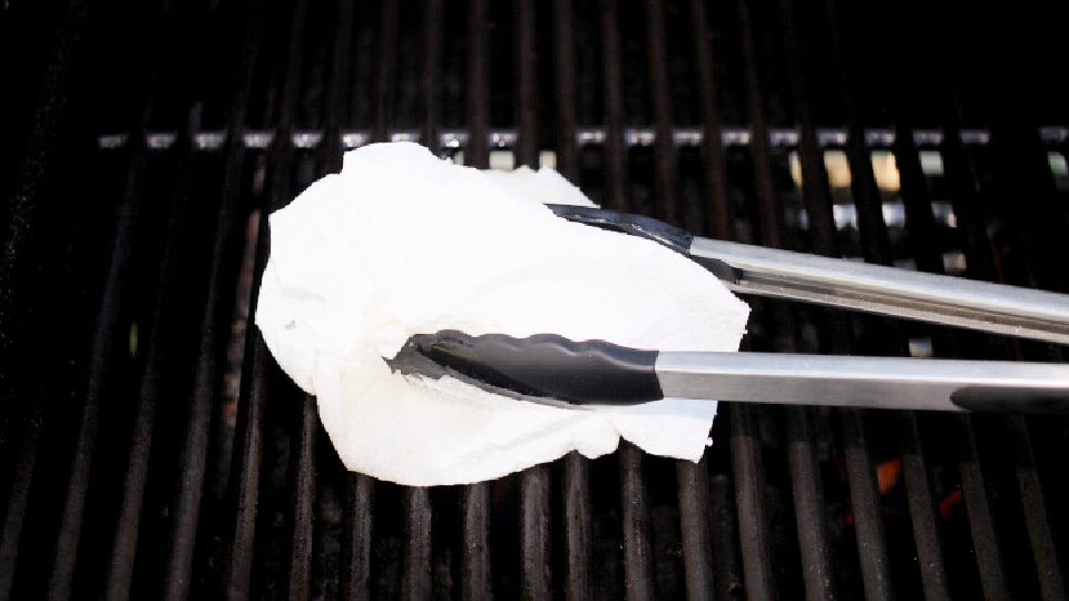 Using a set of long tongs and a wad of paper towels dipped in oil to grease the grill grates before setting salmon on it.