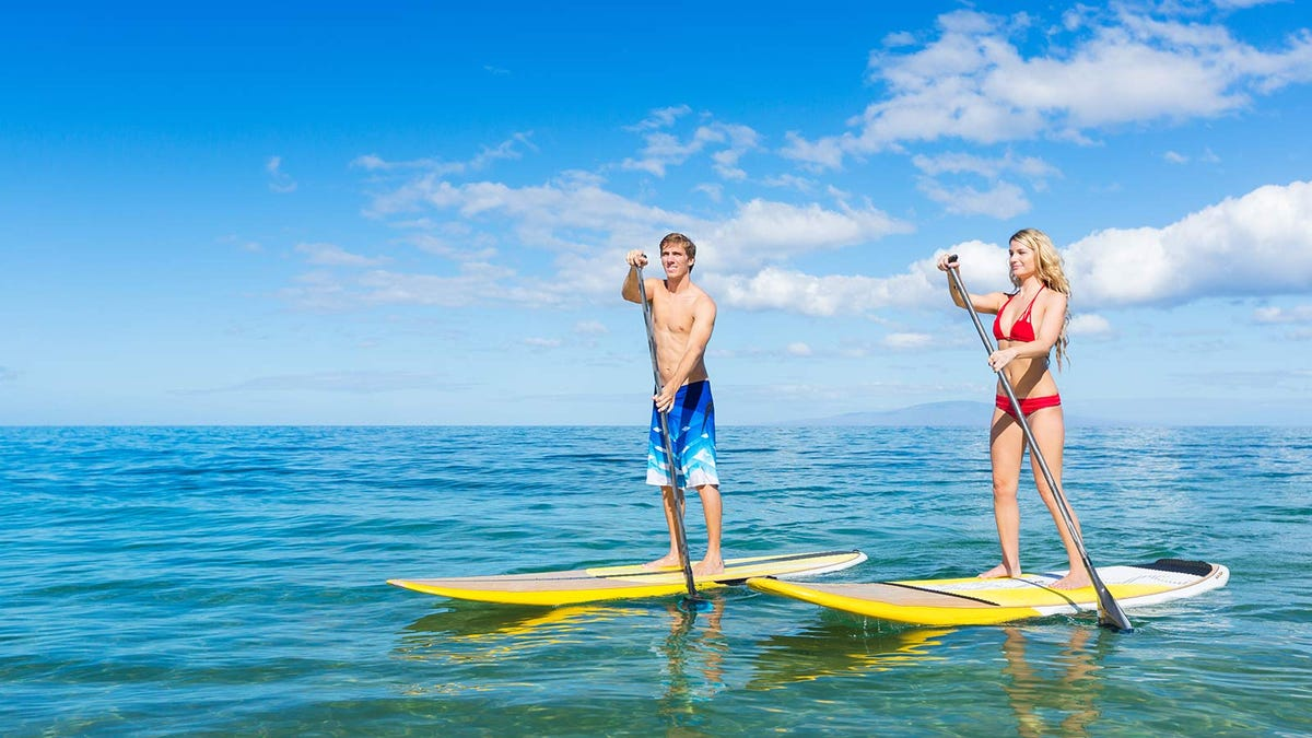 A man and woman paddleboarding.