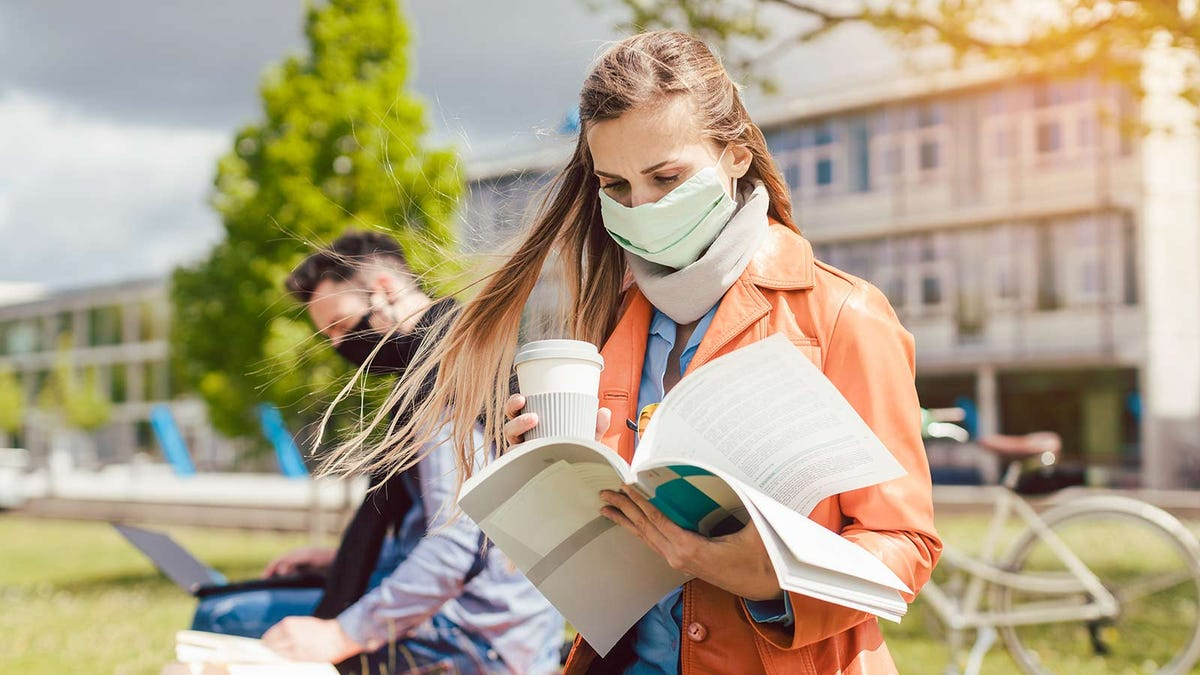 College students sitting outdoors studying, wearing masks.