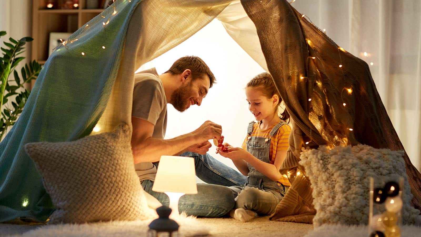 A father and daughter having a tea party in a tent fort.