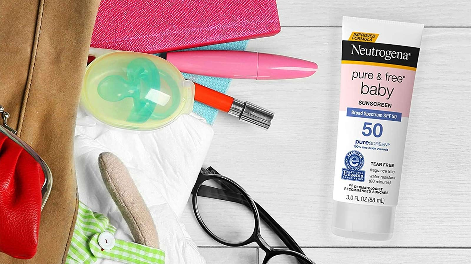A tube of Neutrogena Pure and Free Baby sunscreen on a table next to bag filled with makeup and baby items.