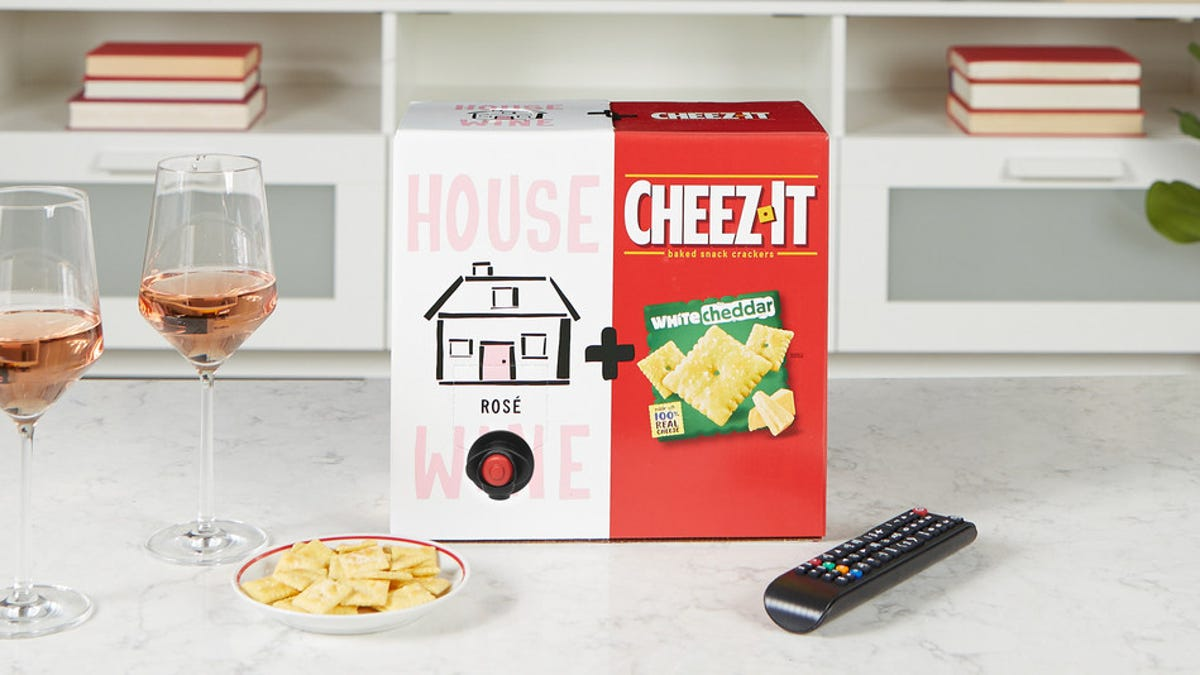 A rosé and cheez-it boxed duo sitting on a marble counter next to two wine glasses and a remote control.