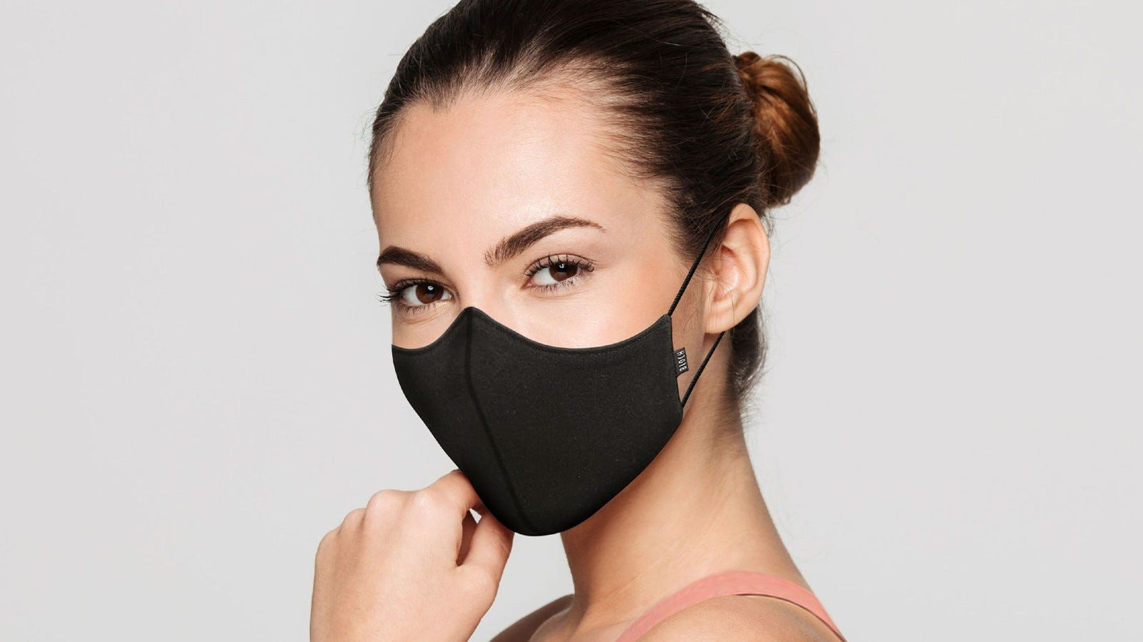 A woman wearing The Well Movement Mask in black.