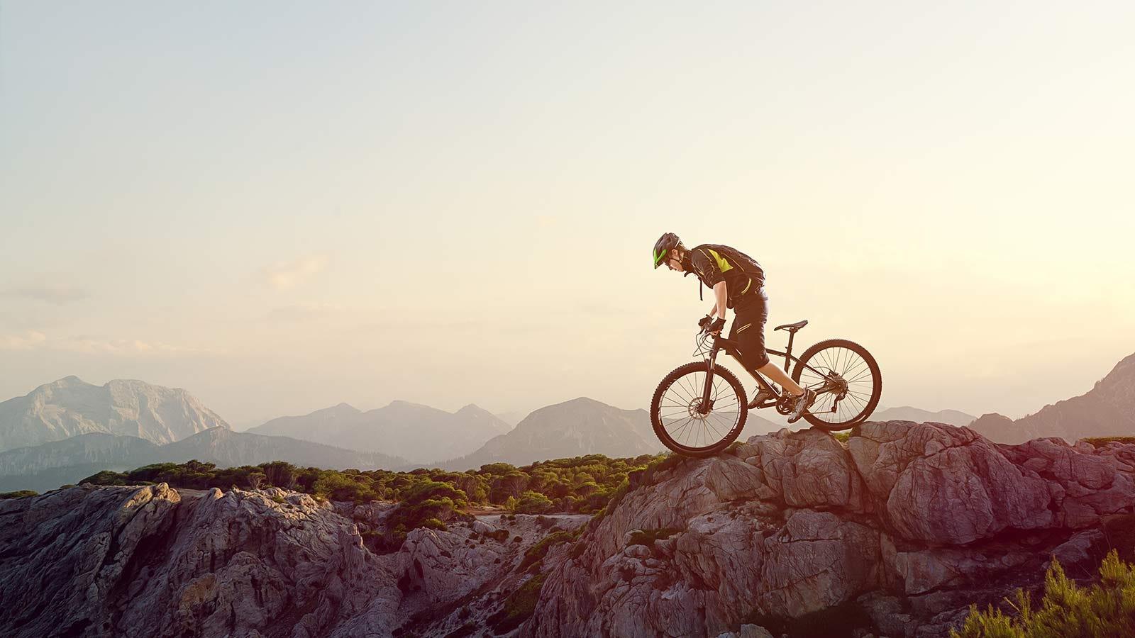 A man carefully riding his mountain bike along a rocky outcropping on a mountain slope.