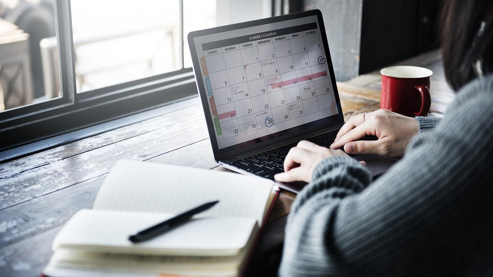 A woman typing something in a calendar on her laptop.