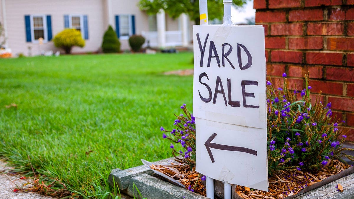 A hand written yard sale sign on the curb outside a home.