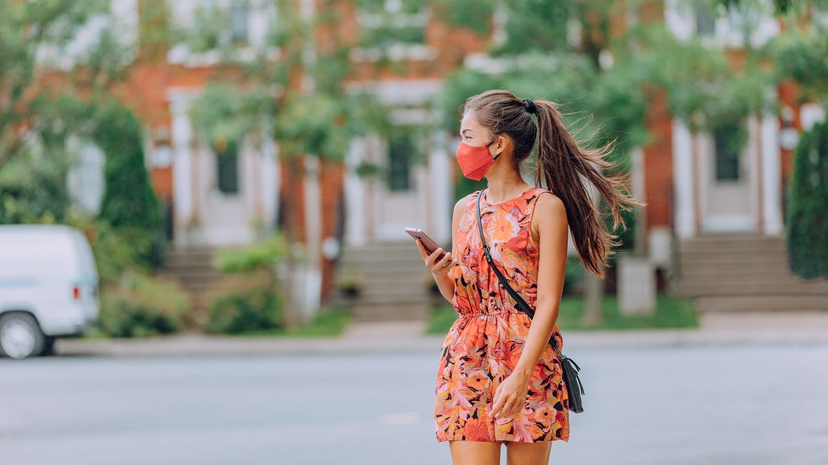 A young woman walking on the street in a summer dress, wearing a matching face mask.