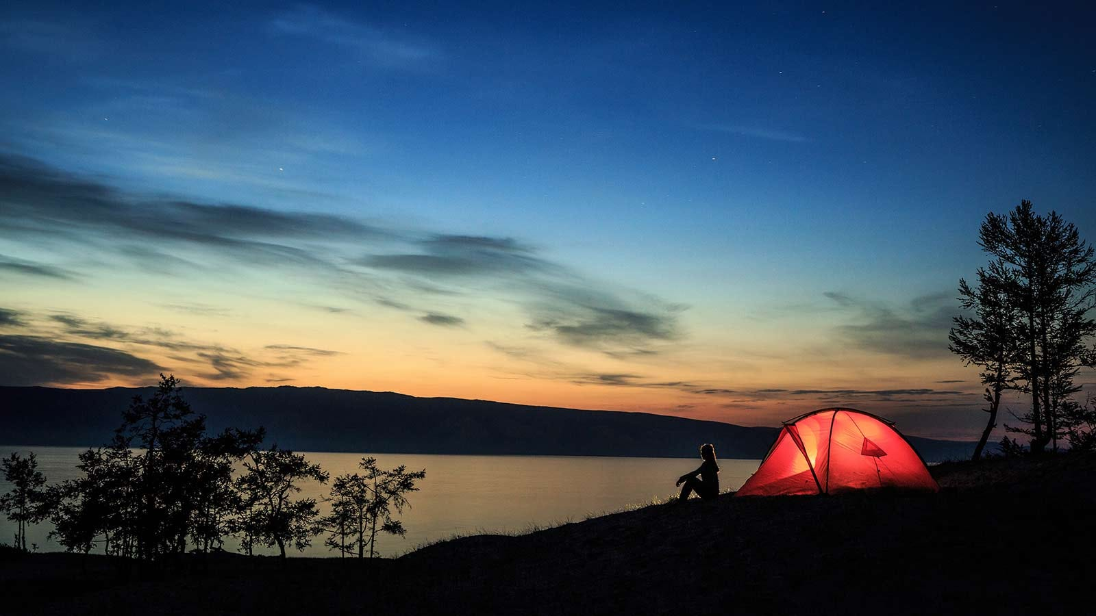 Silhouette of a woman sitting outside an illuminated tent by a remote lake.
