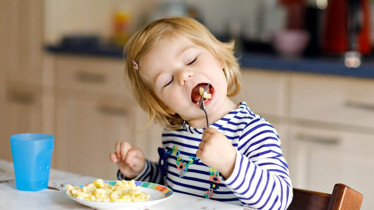 A little girl eating macaroni and cheese.