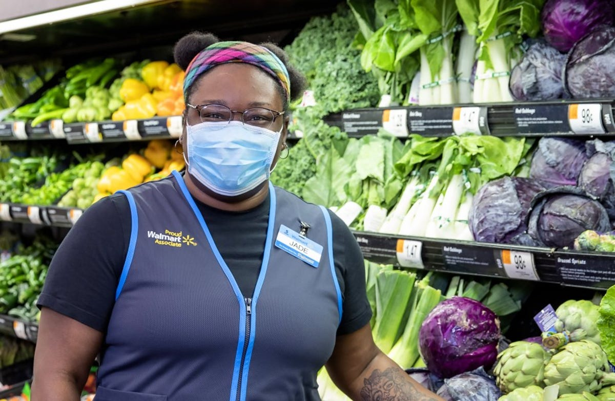 A woman stocks vegetables in a Walmart.
