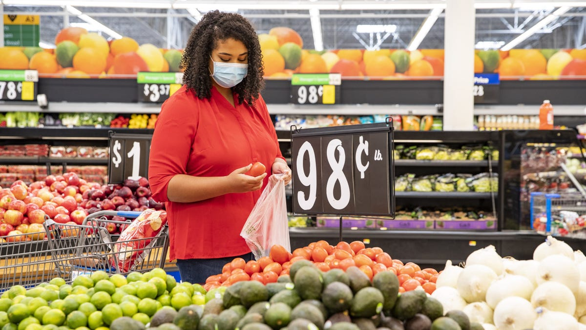A woman browses fruit while wearing a face mask.