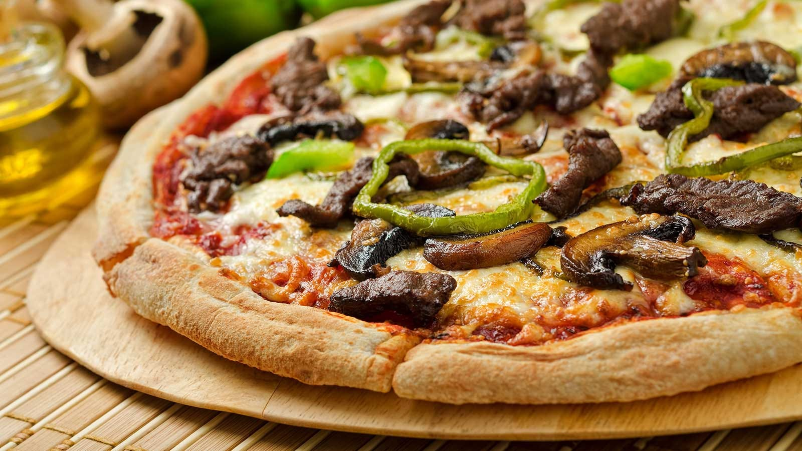 A pizza topped with chopped steak, green peppers, and mushrooms.