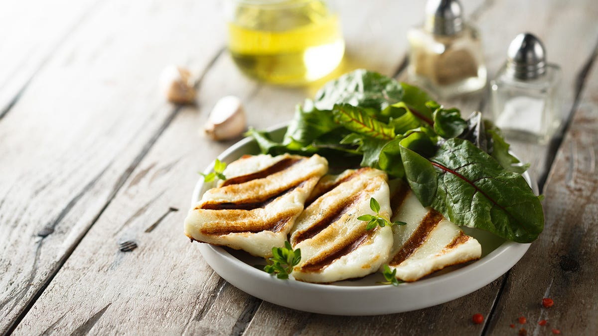 A plate of freshly grilled halloumi cheese on a plate.