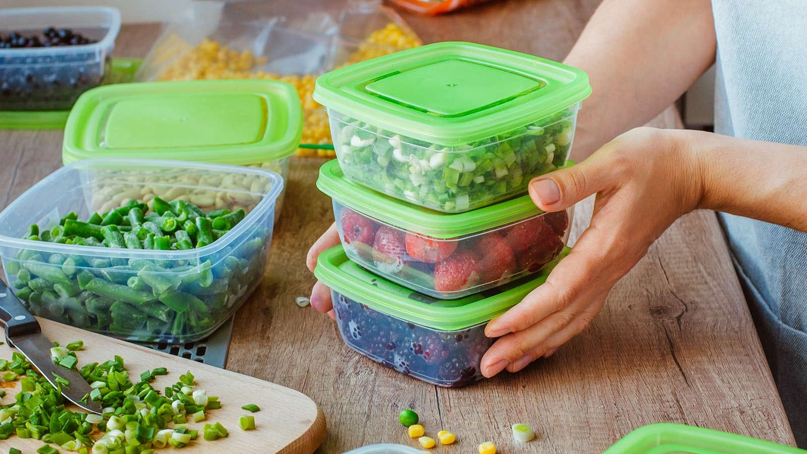 Someone stacking food storage containers filled with fruits and veggies.