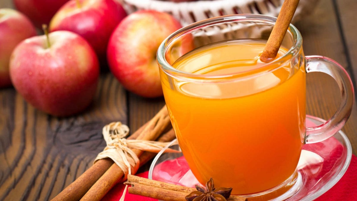 A cup of apple cider with a cinnamon sticks sits among a group of apples.