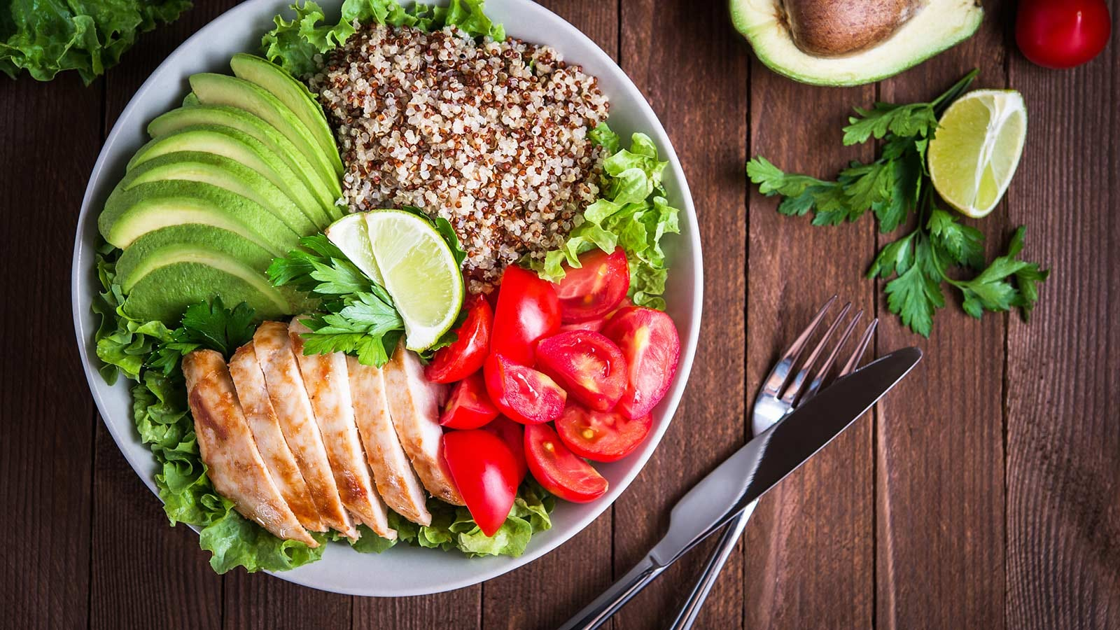 A plate loaded with salad and quinoa, and sliced tomatoes, chicken, avocados, and limes.