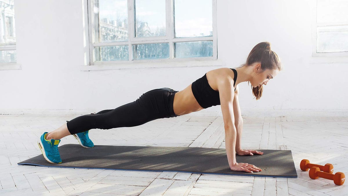 A woman doing push-ups on a yoga mat.