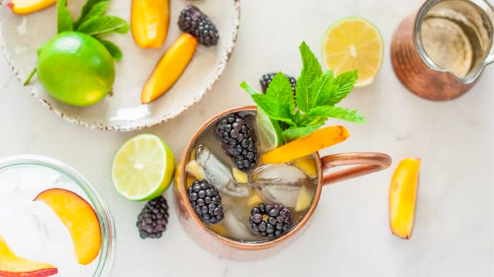 A mocktail mule filled with peaches, blackberries and garnished with a mint sprig.