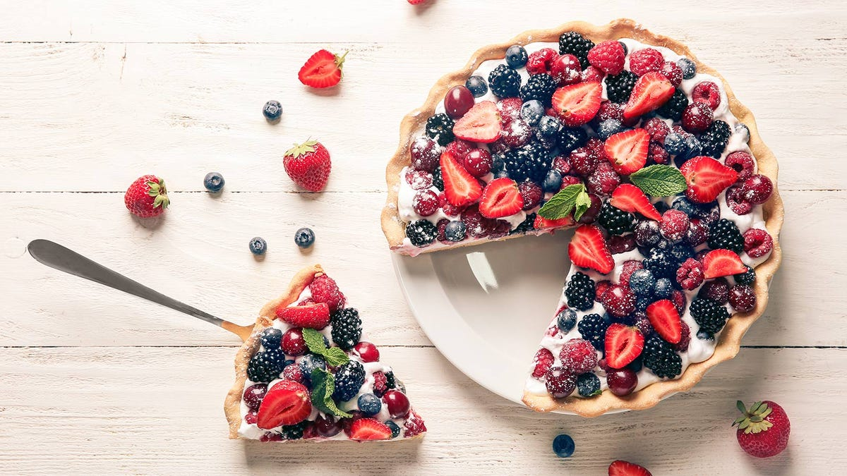 A mixed-berry pie sitting on a white wooden table.