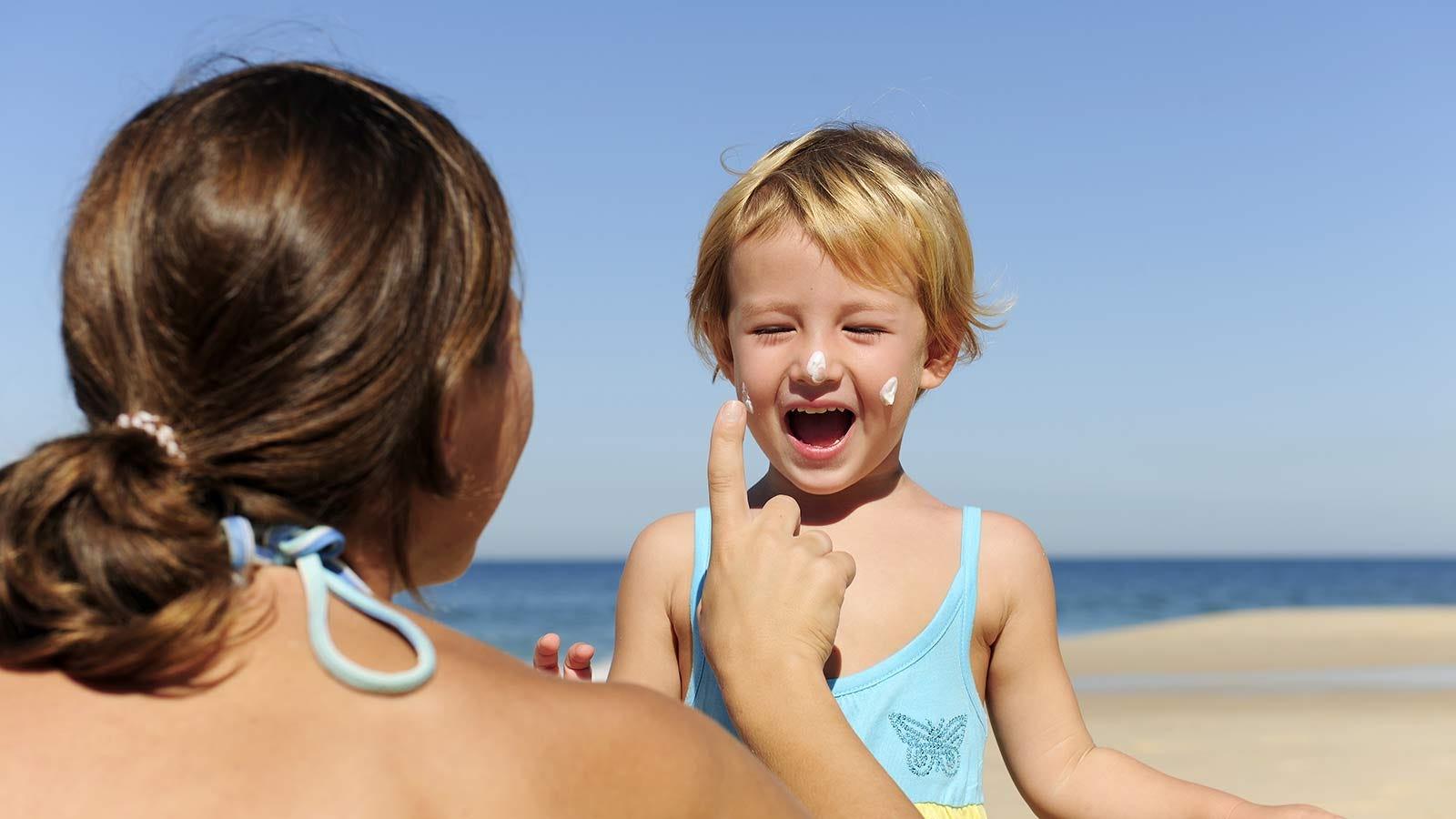 A woman applying sunscreen to a little girl's face.