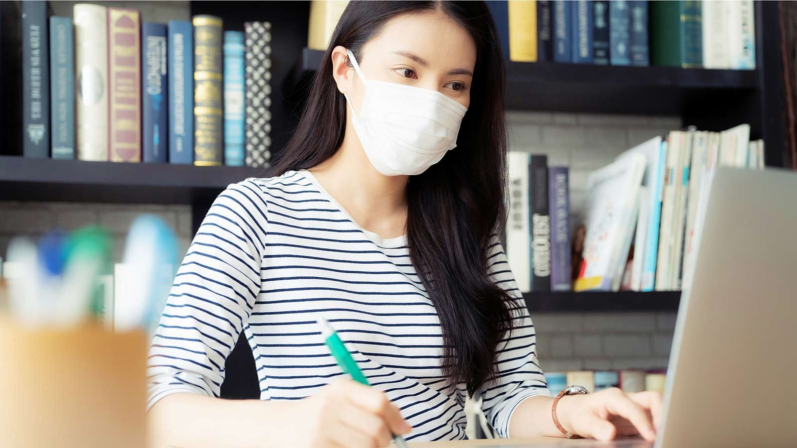 A young woman studying in a college library wearing a mask.