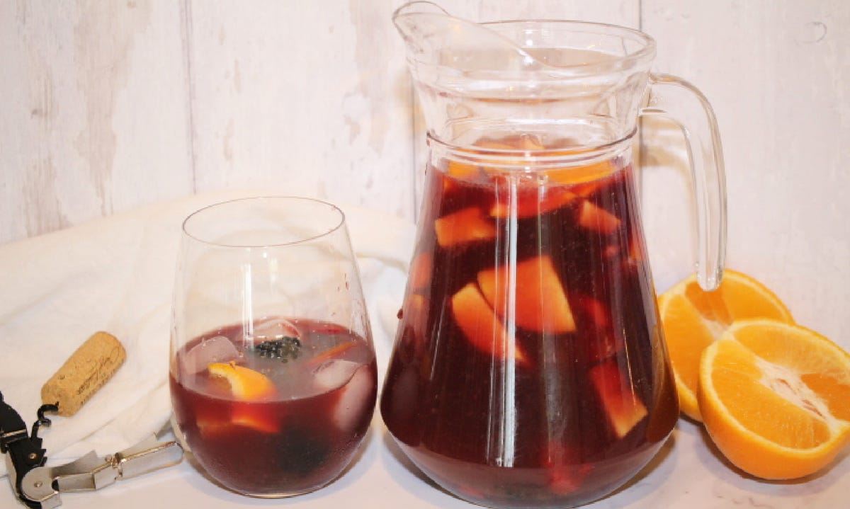 A fresh pitcher of traditional sangria, with a halved orange, a wine opener and a glass of sangria to accompany the pitcher.