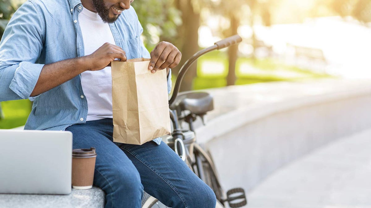 A man eating a packed lunch, sitting on a park wall next to his bicycle.