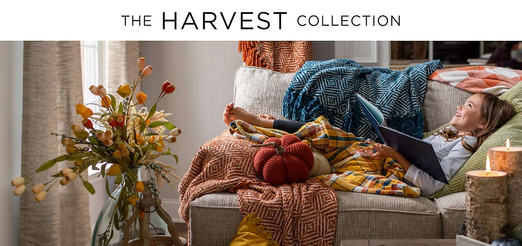 A little girl curled up on a couch with blankets and a book in a room decorated with harvest themes.