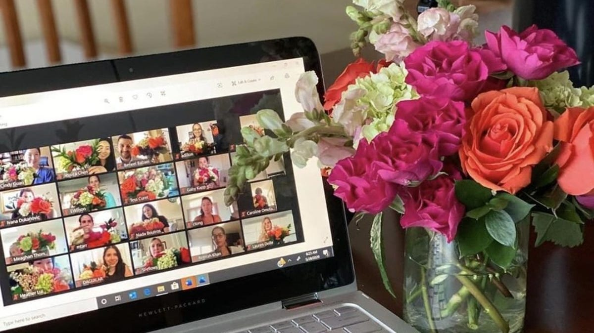 A bouquet of flowers sits next to a computer with a virtual floral arrangement class.