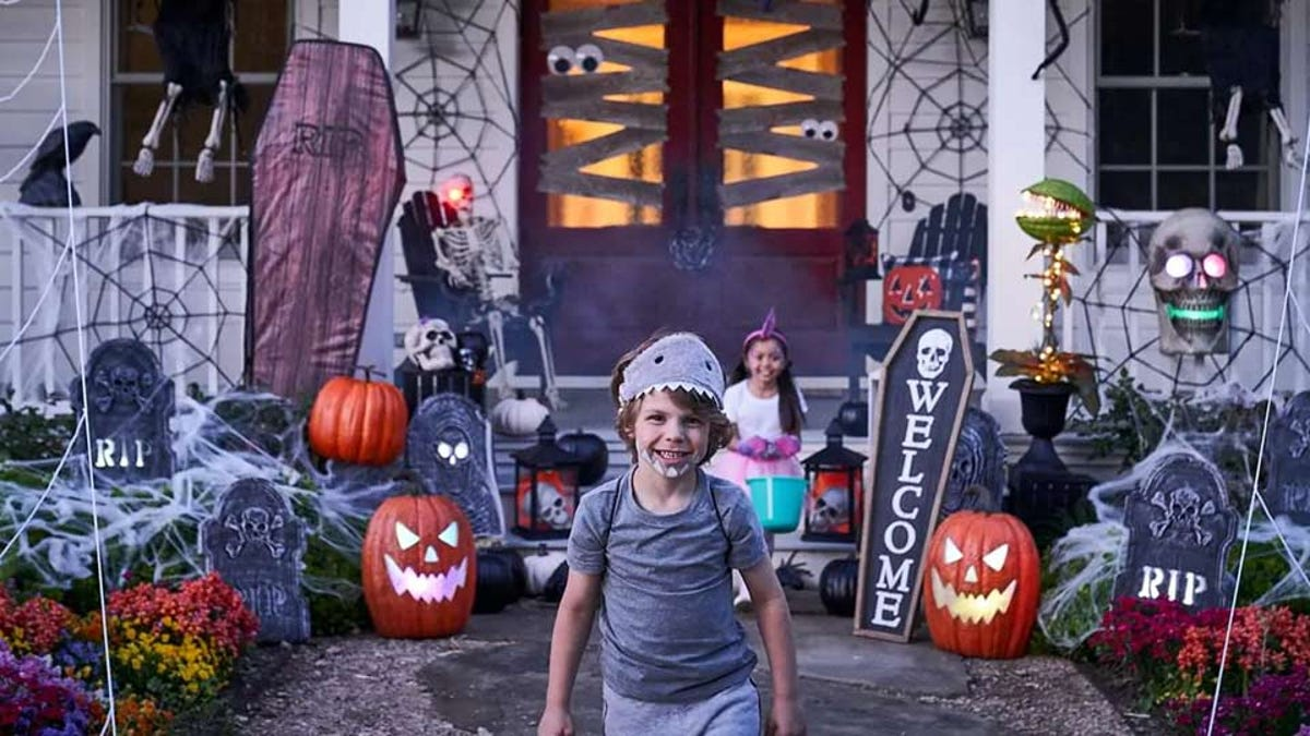 Two kids wearing costumes in front of a house covered in Halloween decorations.