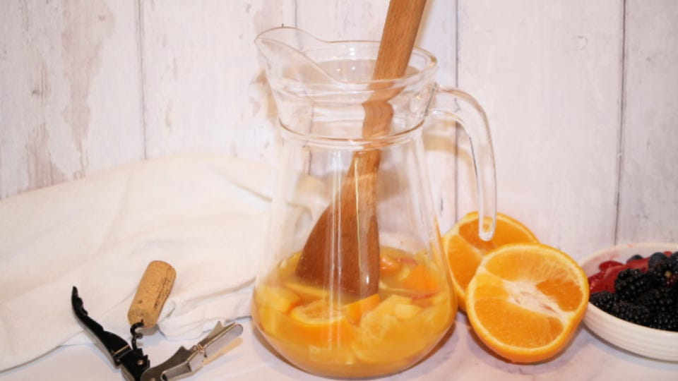 A wooden spoon muddling orange and peach slices and orange juice in a pitcher.