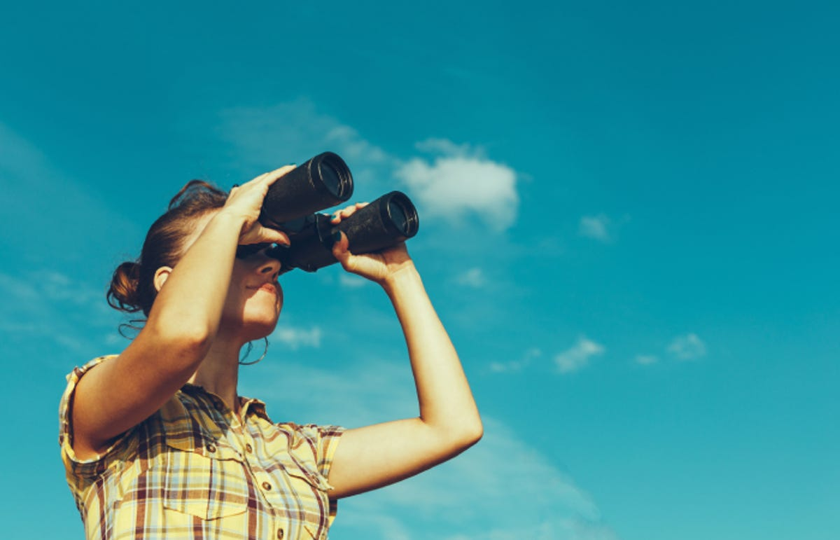 young woman looking through binoculars with a blue sky background