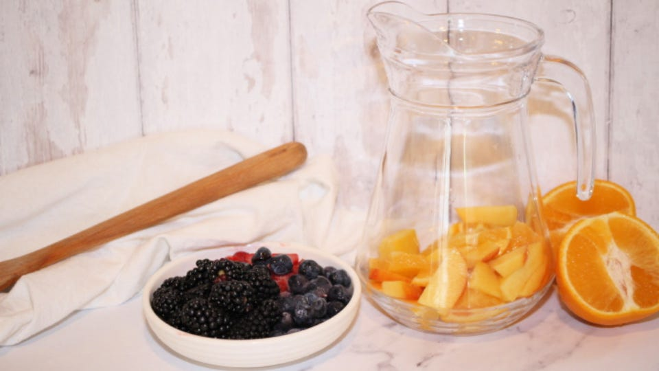 A pitcher with orange and peach slices in it sitting next to a plate of berries.