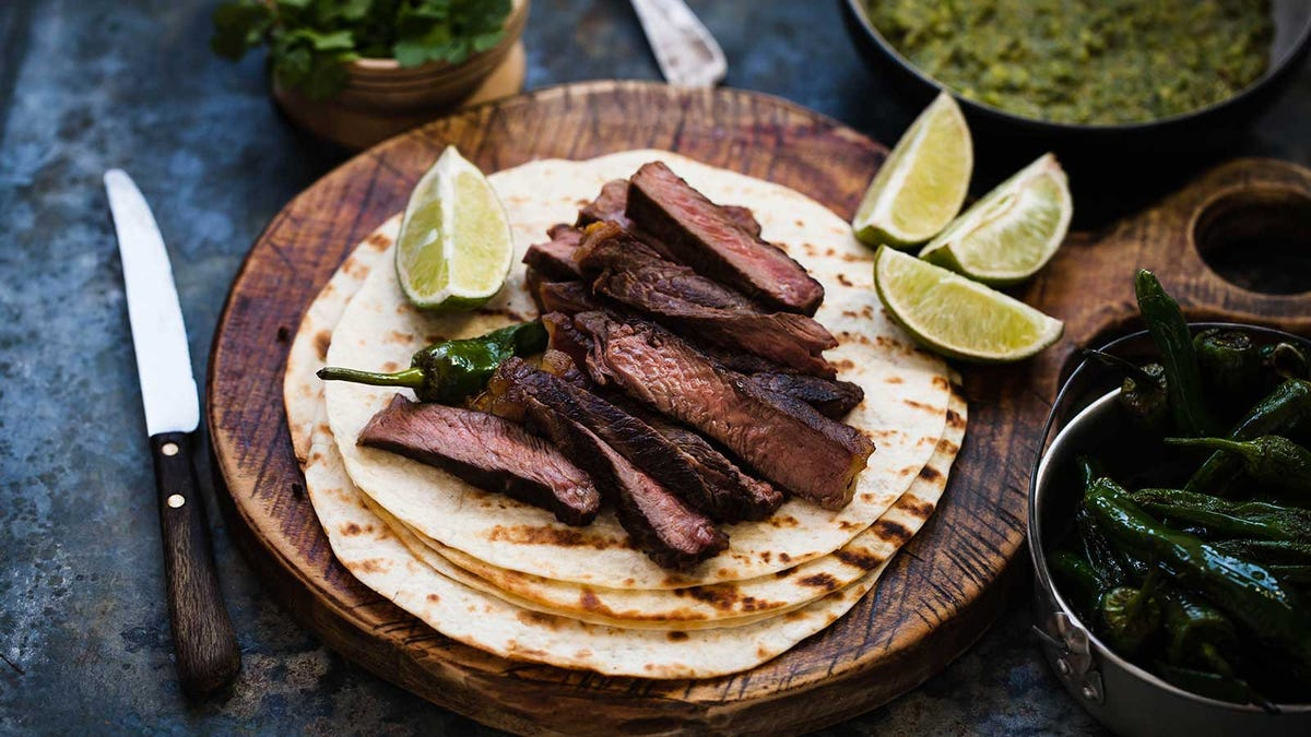 Strips of steak sitting on top of a stack of flour tortillas.
