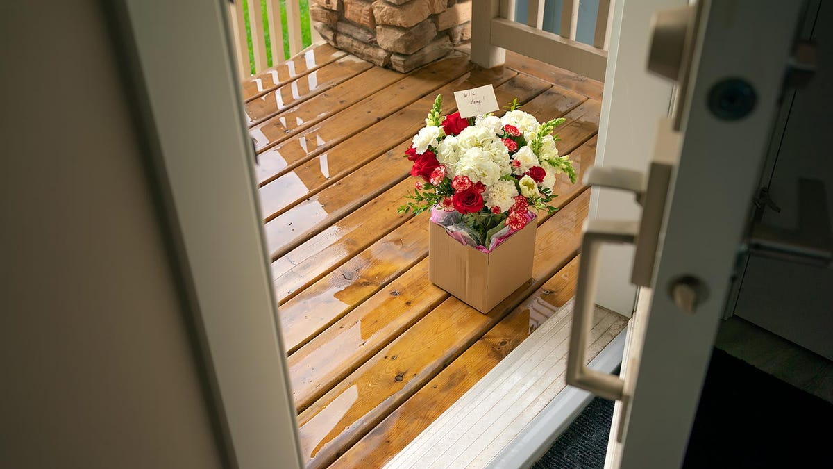 A delivery of flowers sitting outside a front door.