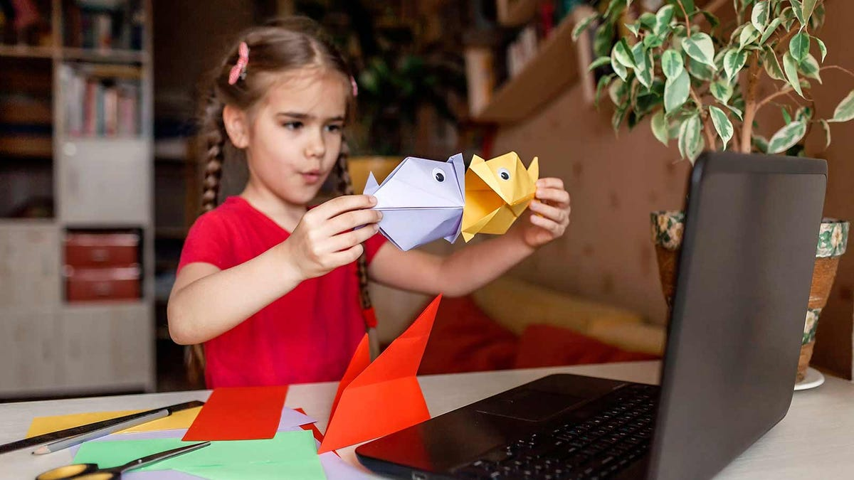 A young girl showing off camp crafts she made at home while participating in a virtual summer camp.