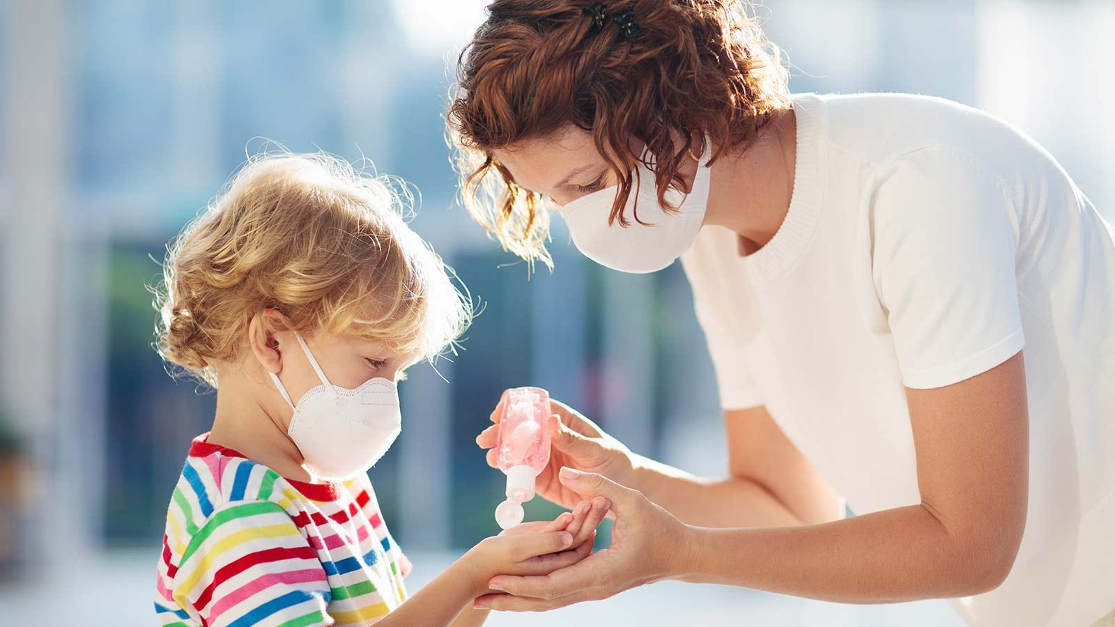 A mother and child, both wearing masks, using hand sanitizer.