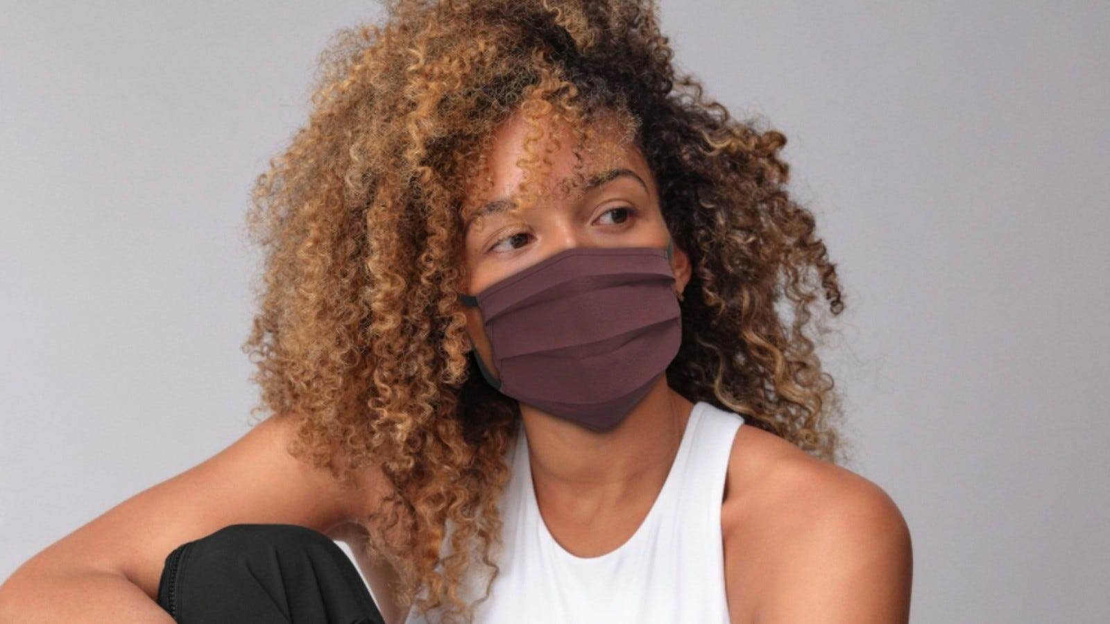 A woman wearing a brown Athleta Everyday Non-Medical Mask.