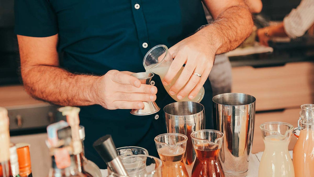A man mixing up some delicious cocktails at a well stocked home bar.