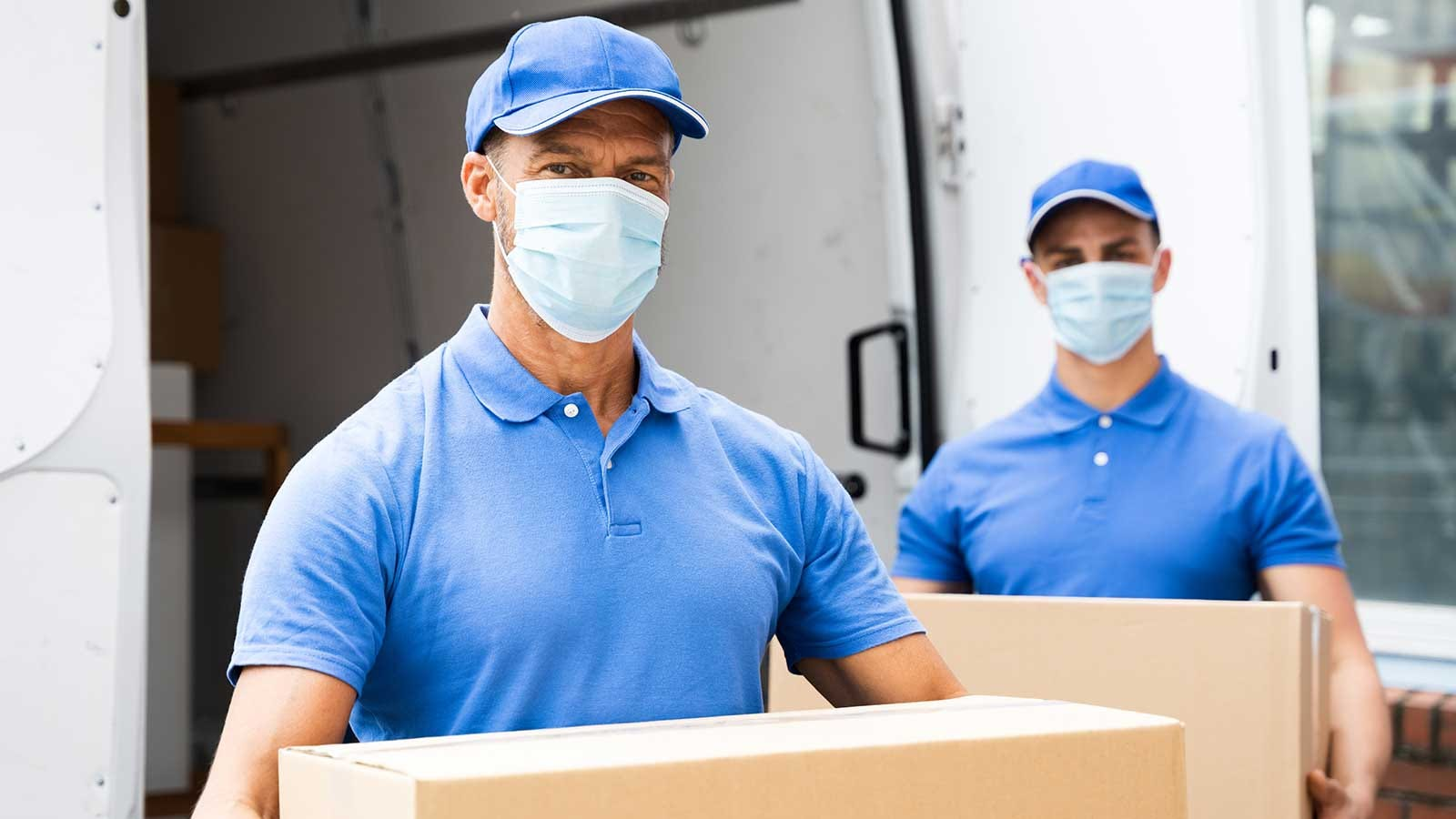 Movers wearing masks, carrying boxes into a new home.
