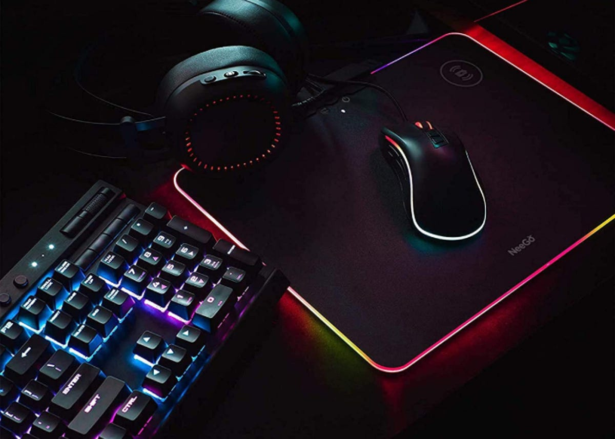 black, rainbow lit charging pad beside a keyboard and supporting a computer mouse