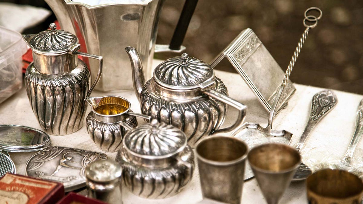 Antique metalware laid out on a table at an estate sale.