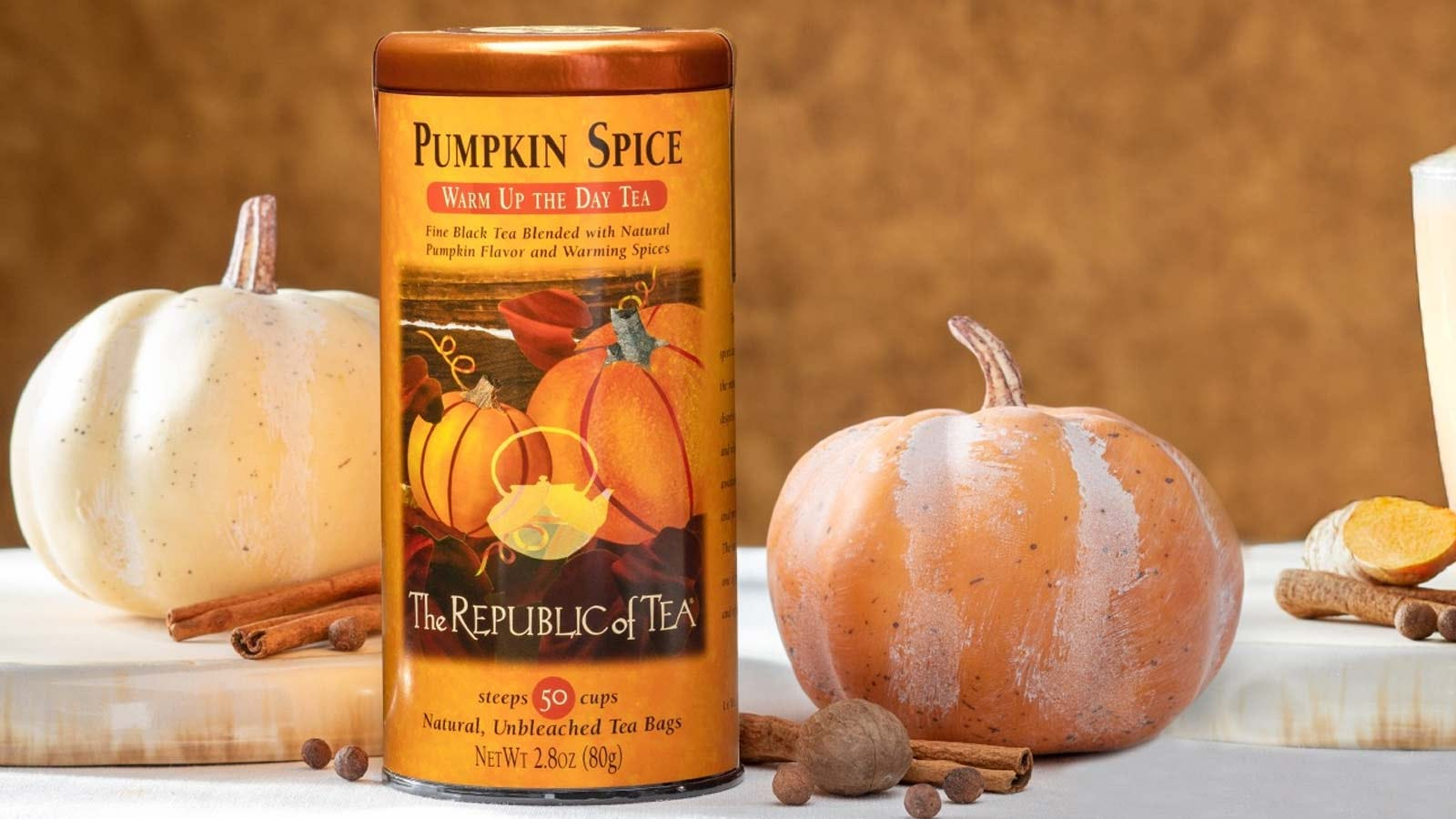 A canister of Pumpkin Spice tea, from The Republic of Tea, sitting on a table with spices and pumpkins.
