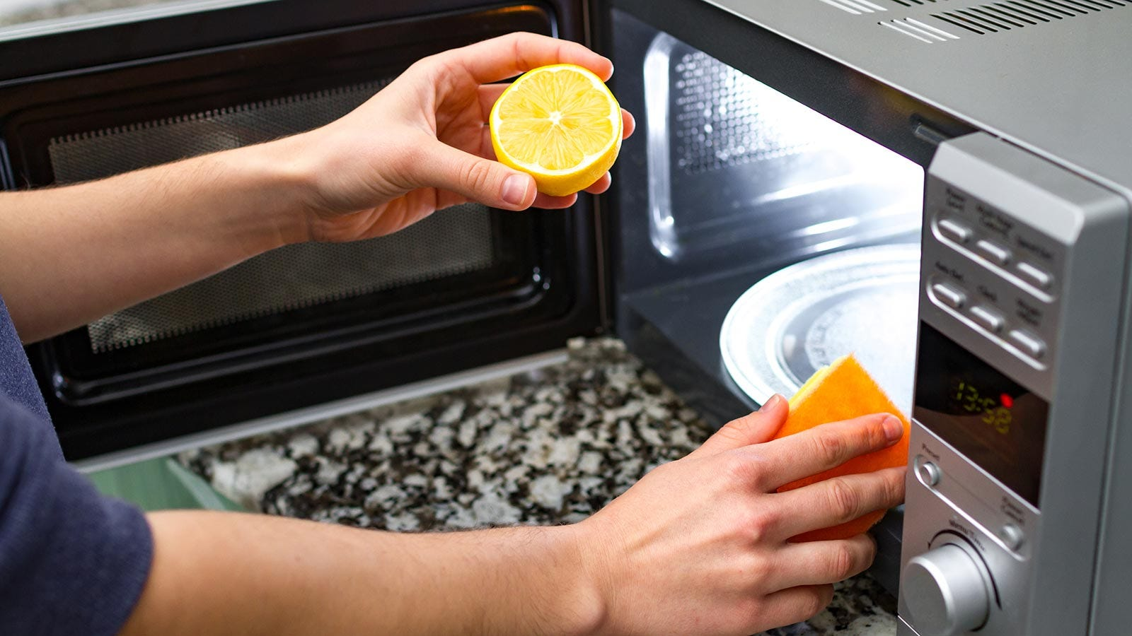 A woman cleaning her microwave with a lemon and sponge.