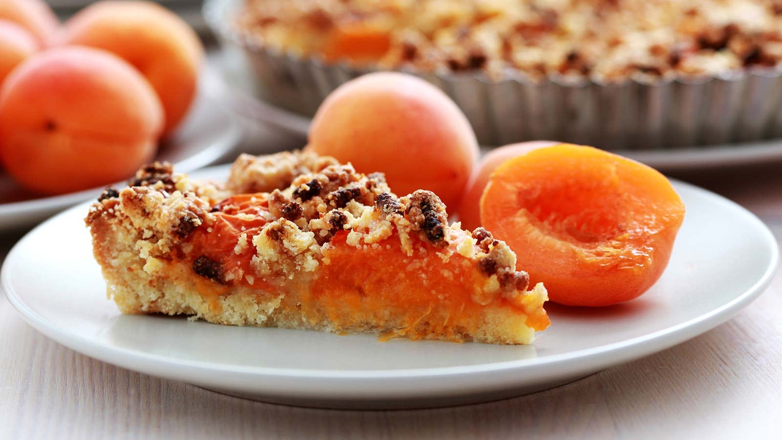 A fresh slice of apricot pie on a plate next to fresh apricots.