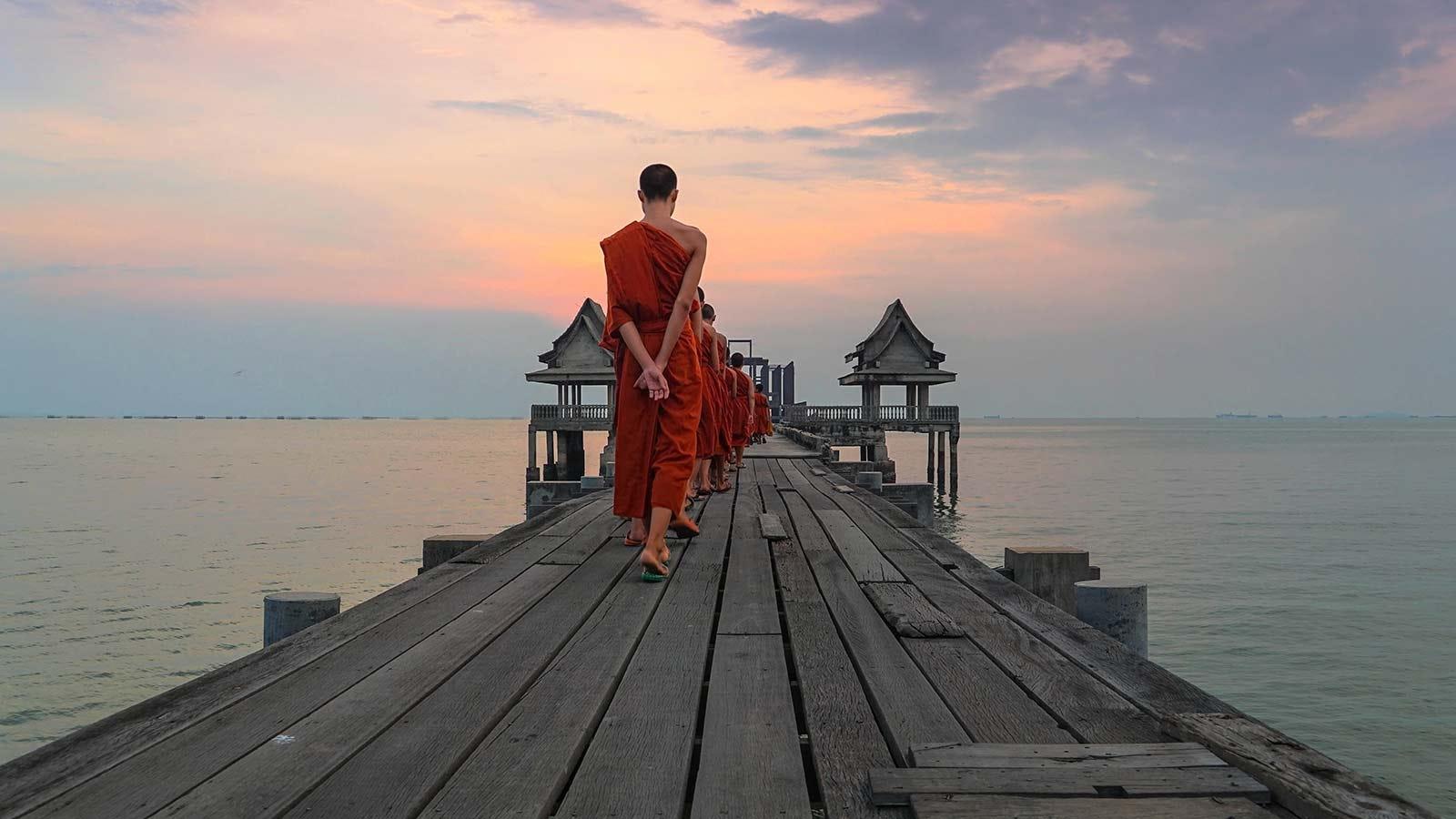 Monks walking down a wooden dock.