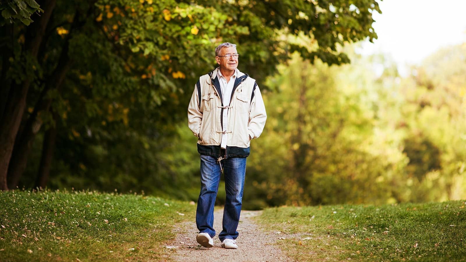 An older man walking in the park, reflecting as he strolls.