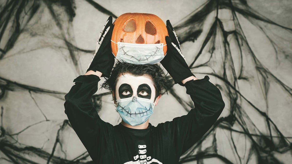 A boy wearing a skeleton costume and matching face mask, holding a jack-'o-lantern.